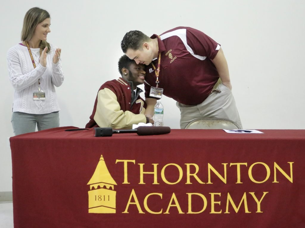 Johnny Rosario is congratulated by Nick Tabor, the offensive line coach for the Thornton Academy football team, after Rosario signed a letter of intent on Wednesday morning at Thornton Academy to play football for the University of Maine. Tabor, along with his wife Danielle, at left, is also a dorm parent to students, including Rosario, in Thornton's residential student program.