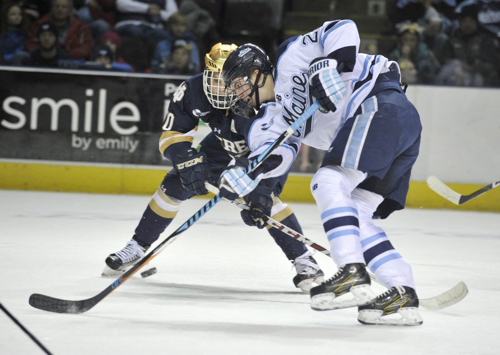 Maine forward Peter Housakos, 24, battles Notre Dame's Anders Bjork for a loose puck in February.