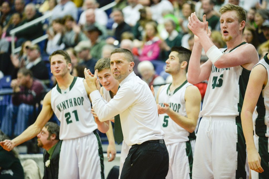 Winthrop Coach Todd MacArthur and his team celebrate in the fourth quarter of the Class C North boys' basketball semifinal game against NYA on Thursday. The Ramblers won 52-29.