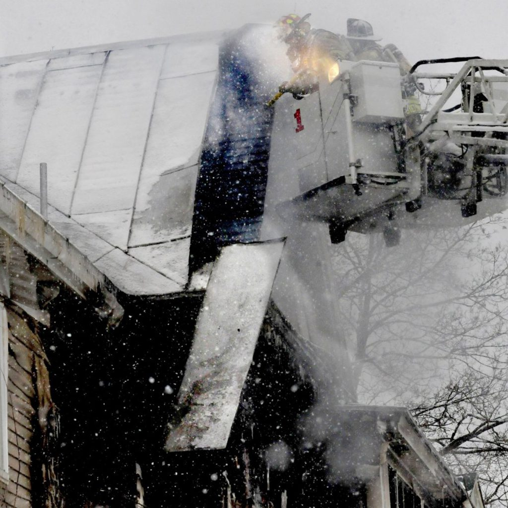 Firefighters working from a ladder truck pull off roofing material to put out a stubborn fire that destroyed an apartment building on Summer Street in Waterville early Wednesday morning as light snow fell.