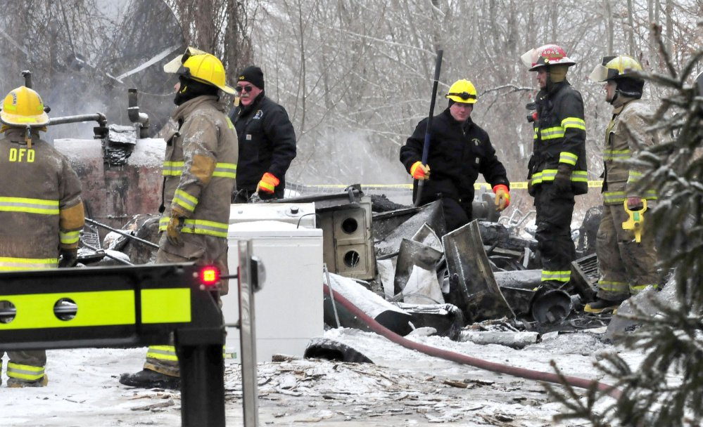 Stu Jacobs, left center, and Jeremy Damren of the Fire Marshal's Office and firefighters investigate the section of an apartment building in Palmyra where the bodies of two people were recovered on Tuesday.