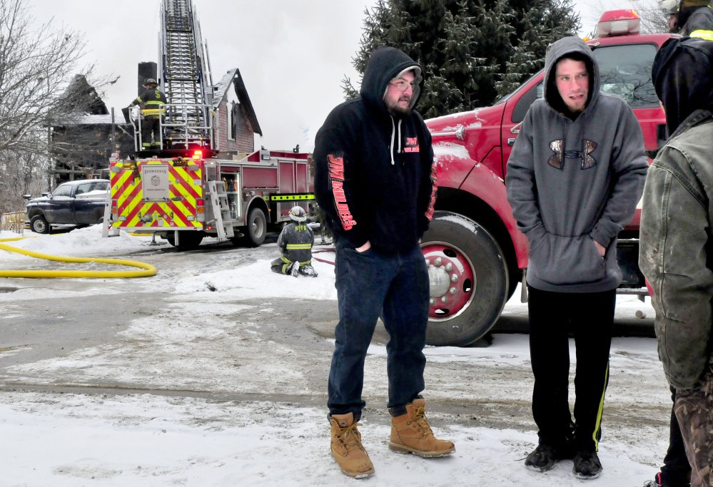 Tenants Joshua Lombard, left, and Jordan Ballard talk with friends as firefighters put out the fire that destroyed an apartment building on Square Road in Palmyra.