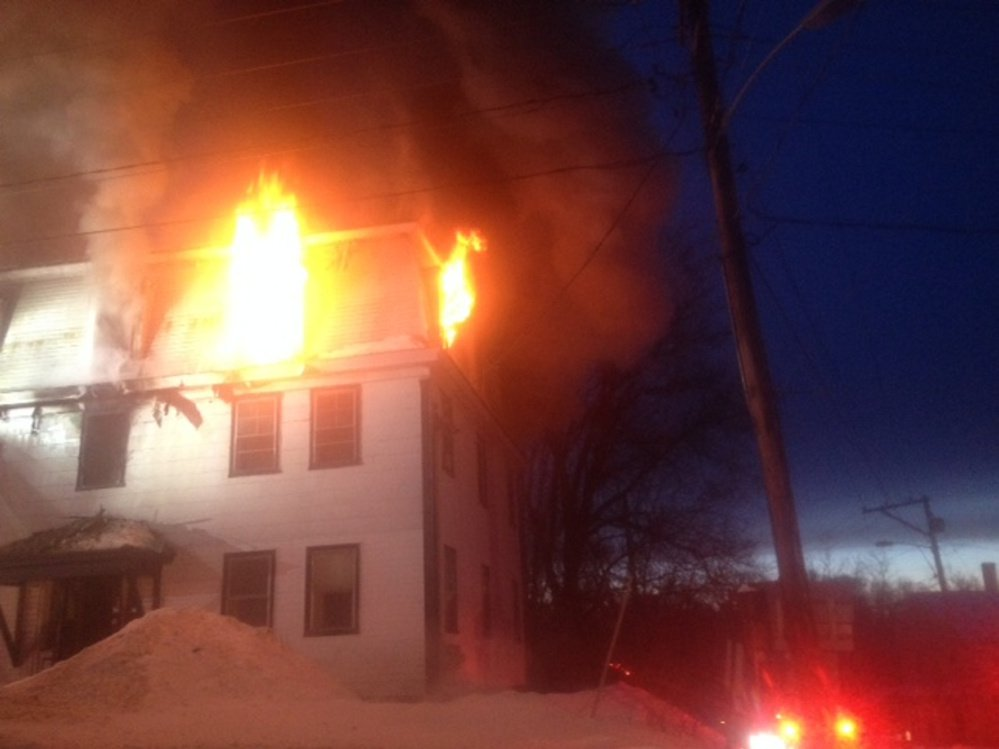Firefighters work at the scene of a fire Tuesday evening at an apartment building at 11 Main St. in Skowhegan.