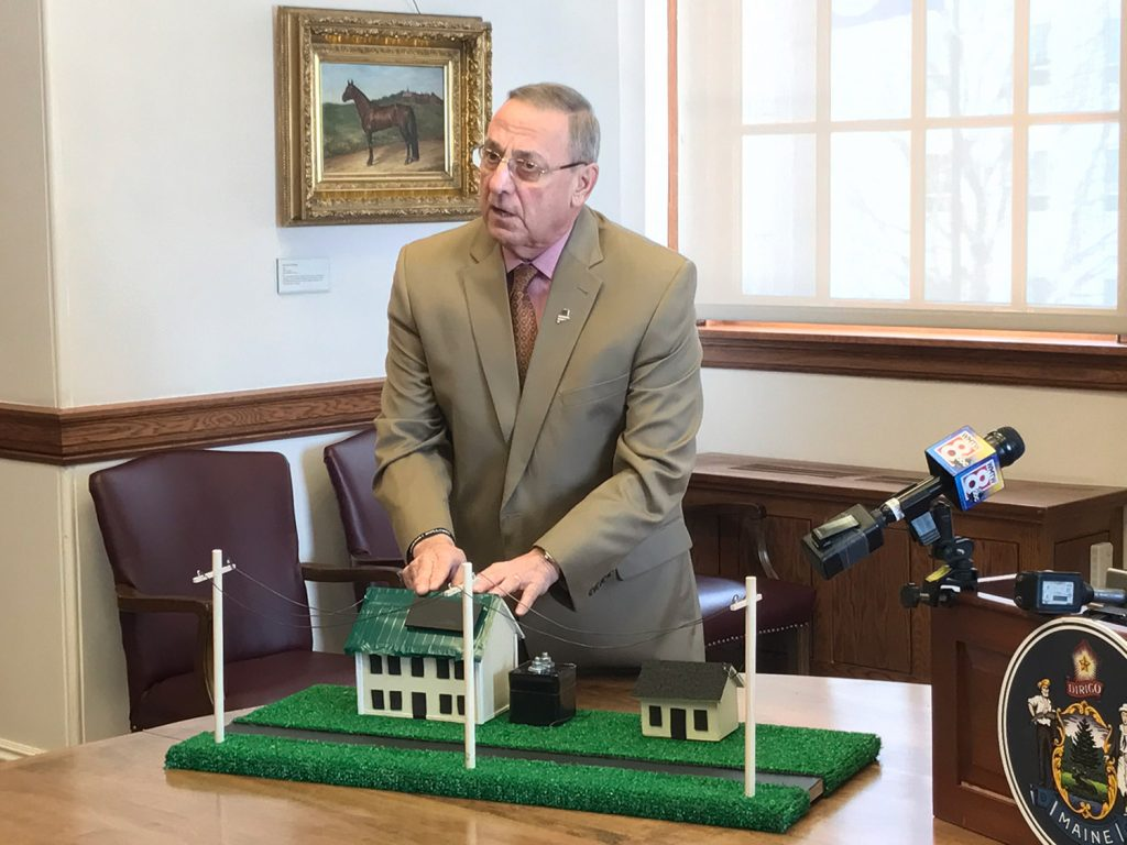 Gov. Paul LePage uses a prop model of two houses to make a point about residential solar energy use on Friday in Augusta.