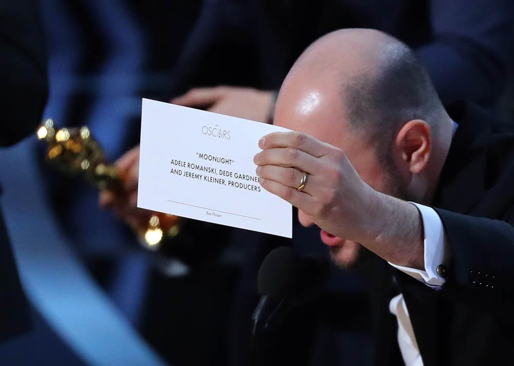 "Producer Jordon Horowitz holds up the card for the Best Picture winner ""Moonlight."""