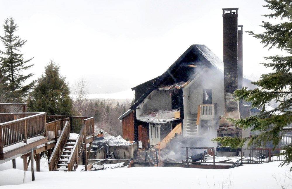Smoke still rises Wednesday beside a bare chimney from the remains of a Rock Pond condominium destroyed by fire Tuesday night at Saddleback Ski resort in Rangeley. Two adjacent condos were also damaged by the wind-swept fire.