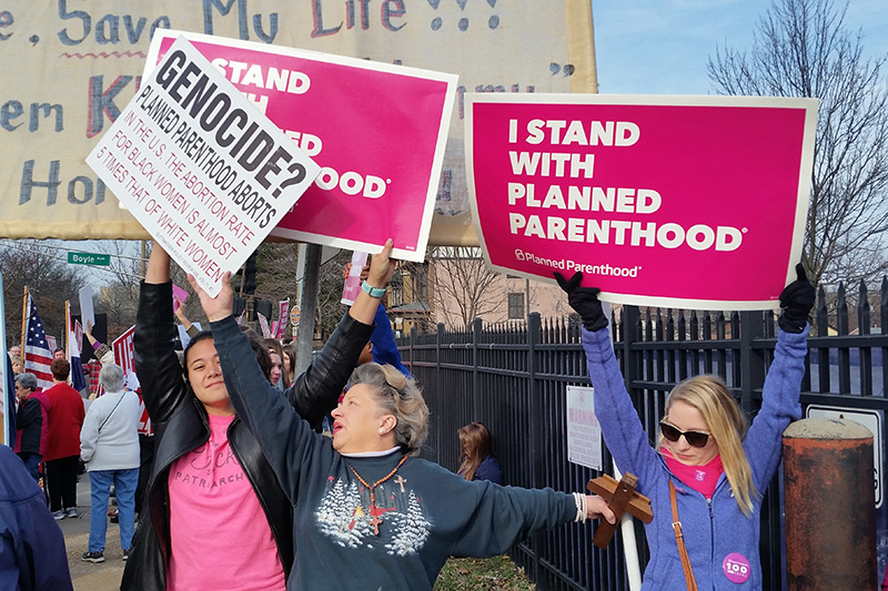 A Planned Parenthood supporter and opponent try to block each other's signs during a protest and counter-protest Saturday  in St. Louis.