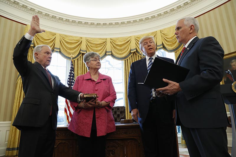 Vice President Mike Pence administers the oath of office to Attorney General Jeff Sessions, accompanied by his wife Mary.