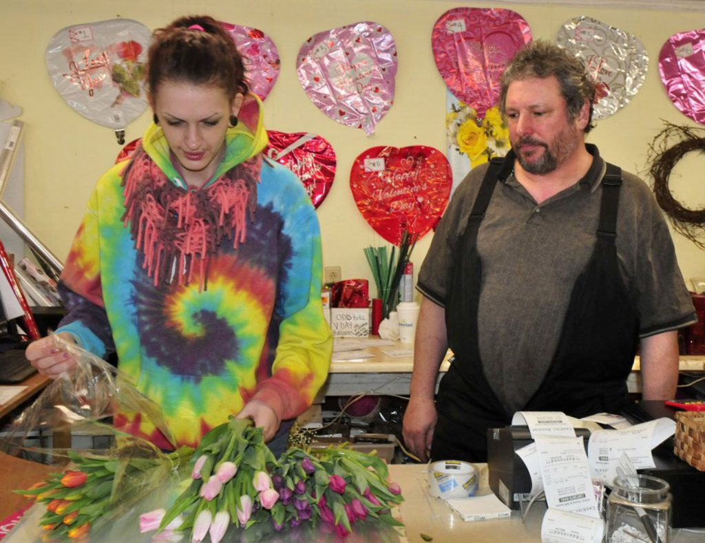 "Dave Lagrange, who owns KMD Florist & Gift House in Waterville, watches as employee Tavia Chamberlain makes a Valentine's Day bouquet on Monday. ""We're going to see how much we can pack into one day that is usually spread over two days,"" Lagrange said."