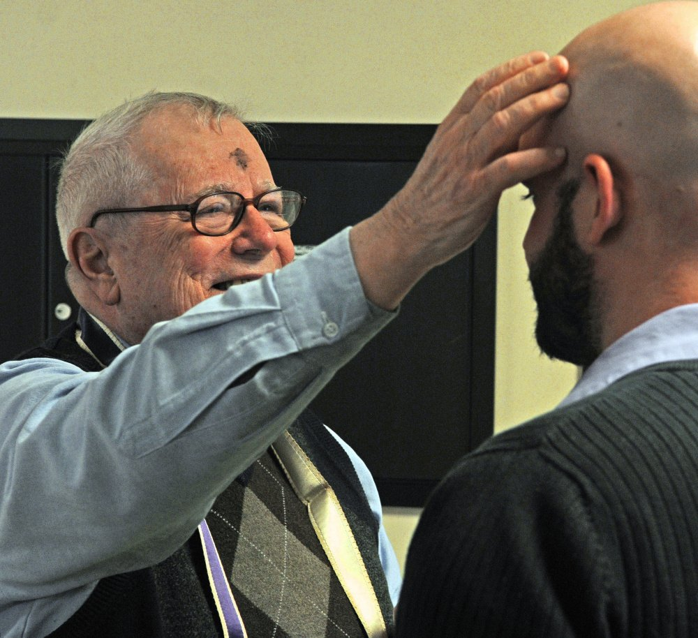The Rev. James Gill applies ashes to Stephen Farrington's forehead Wednesday at the Winthrop Commerce Center. Gill was taking part in the international Ashes To Go program on Ash Wednesday, the beginning of the Christian season of Lent, which leads up to Easter.
