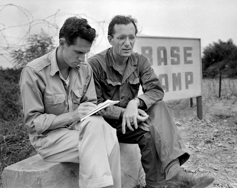 FILE - In this Aug. 1951 file photo, AP staffer Sam Summerlin, left, interviews Robert J. Santucci of Rochester, N.Y., a United Nations civilian stenographer who has been attending the Kaesong meetings, as they sit outside the entrance to the base camp at Munsan, Korea. Associated Press foreign correspondent Summerlin, who flashed the news to the world that the Korean War had ended and who reported on everything from Latin American revolutions to U.S. race riots during a long and distinguished career, has died at age 89. He died Monday, Feb. 27, 2017, at a care home in Carlsbad, Calif., from complications of Parkinson's disease, according to his daughter, Claire Slattery of Encinitas, Calif. (AP Photo/Bob Schutz, File)