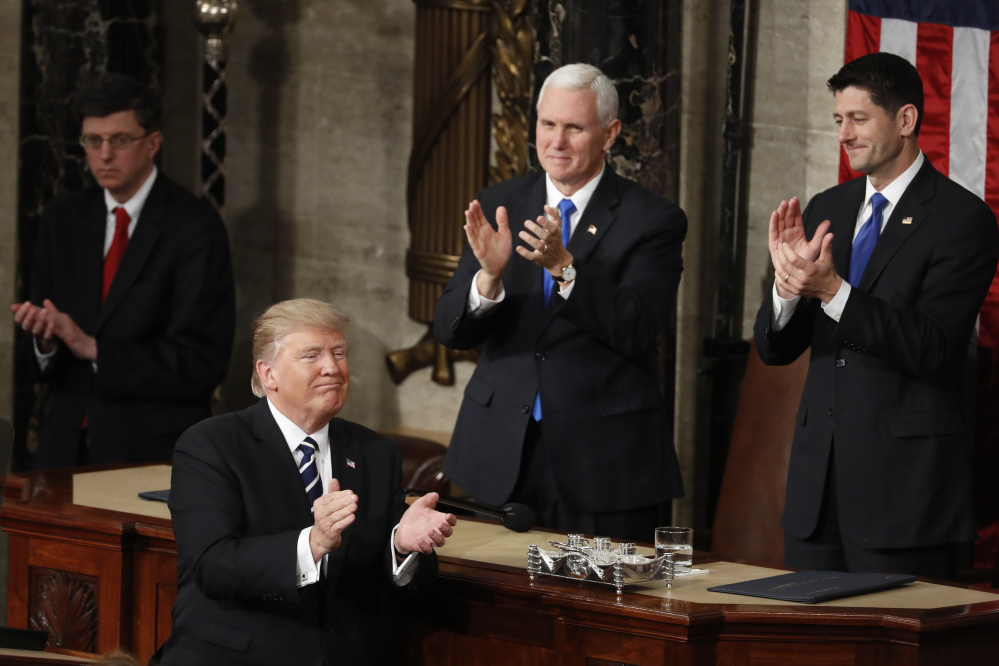 Vice President Mike Pence and House Speaker Paul Ryan applaud as President Trump concludes his speech to Congress on Tuesday. Trump won high marks from Republicans for his agenda and his measured tone.