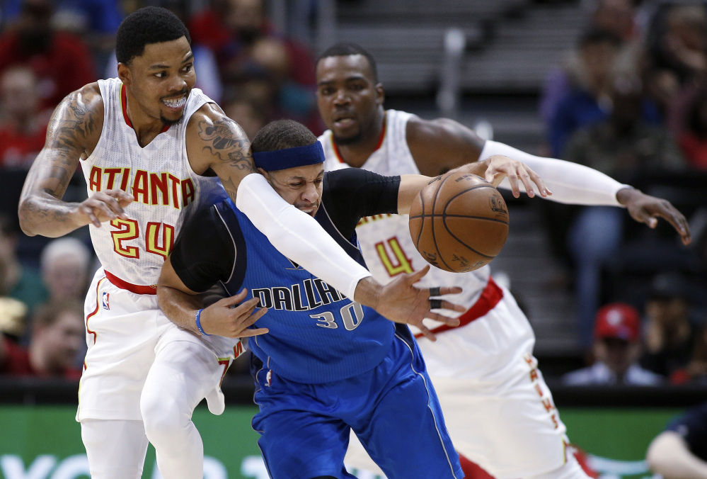 Seth Curry of the Dallas Mavericks, center, attempts to maintain control of the ball Wednesday night while pressured by Kent Bazemore, left, and Paul Millsap of the Atlanta Hawks during the first half of the Hawks' 100-95 victory at home.