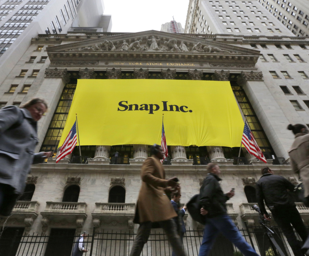 People pass by the New York Stock Exchange after the banner for the Snap Inc. IPO was raised on the building's facade Wednesday. Snap Inc. started trading Thursday.