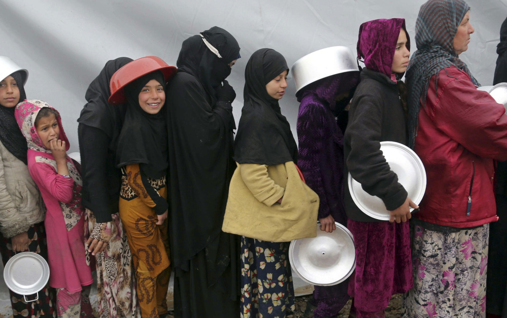 Displaced Iraqis, who fled fighting between Iraqi security forces and Islamic State militants, line up to receive food at a camp south of Mosul on Thursday.