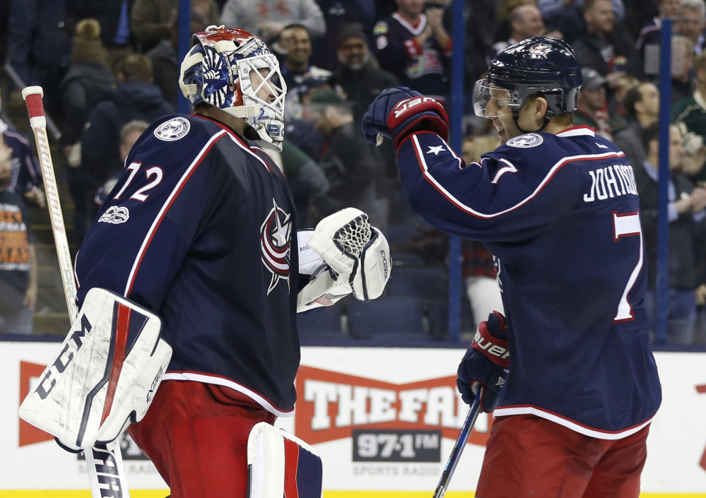 Blue Jackets goalie Sergei Bobrovsky celebrates with Jack Johnson after the team's 1-0 win over the Minnesota Wild on Thursday night. Bobrovsky stopped 38 shots.