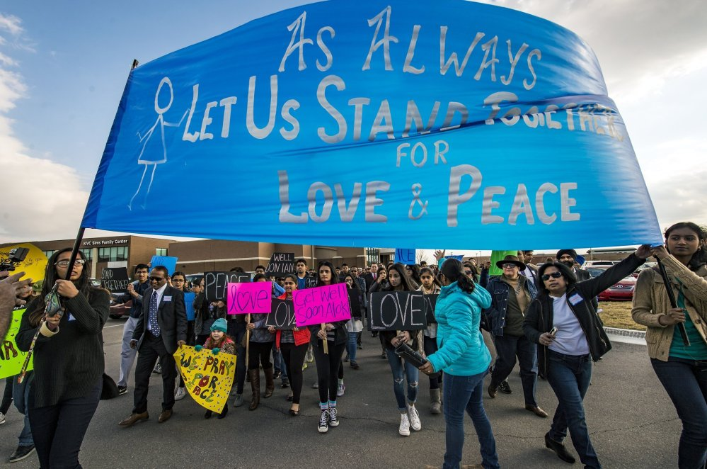 Hundreds of people march for peace Feb. 26 around the Ball Conference Center in Olathe, Kan., before starting a prayer vigil in response to the deadly shooting of two Indian men.