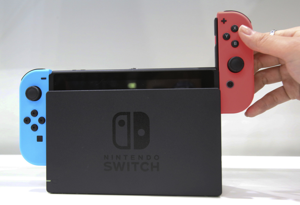FILE - In this Friday, Jan. 13, 2017, file photo, a model puts the controller onto the Nintendo Switch during a presentation event of the new Nintendo Switch in Tokyo. Nintendo's new Switch device aims at video gamers who like to play both at home and on the road. It's an impressive device, notwithstanding trade-offs in appealing to both. The bigger question is whether Nintendo will be able to deliver enough games to keep Switch users happy. (AP Photo/Koji Sasahara, File)