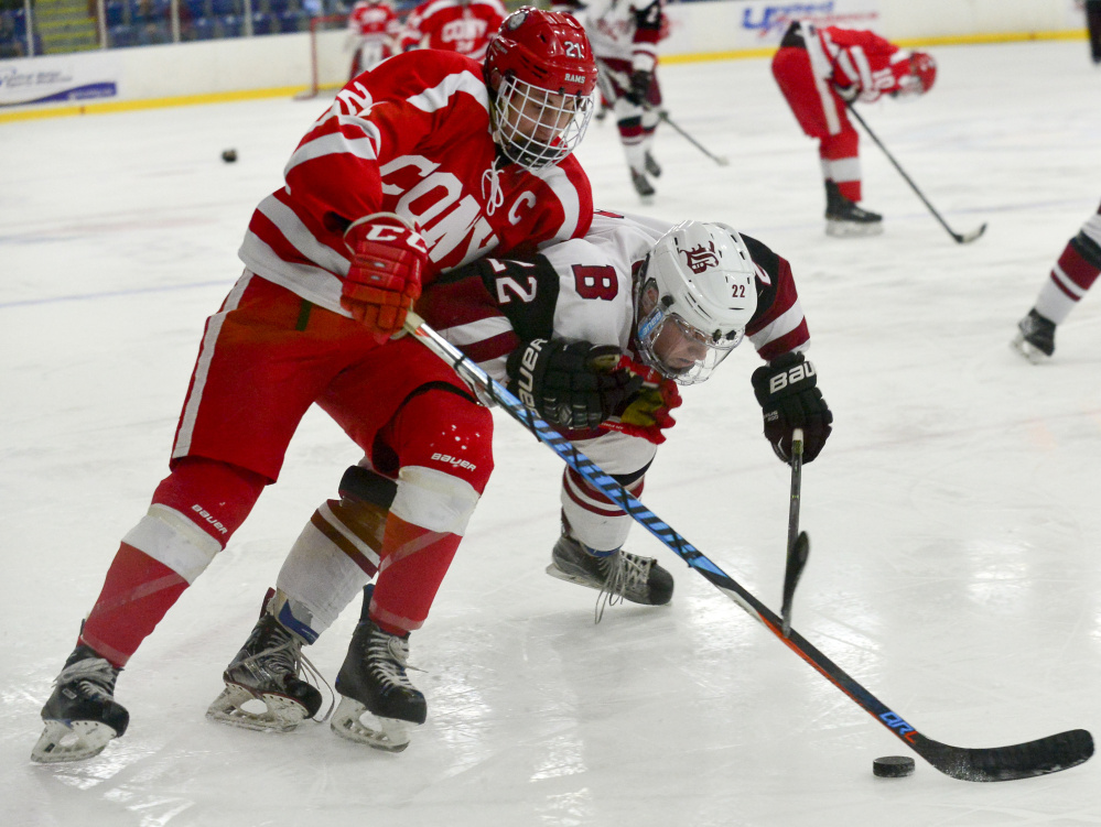 Bangor's Kodi Lagassie, right, smashes into Cony's Thomas Arps in an attempt to gain control of the puck in the second period of the Class A North semifinals Saturday at the Androscoggin Bank Colisee in Lewiston. Bangor went on to win 2-1.