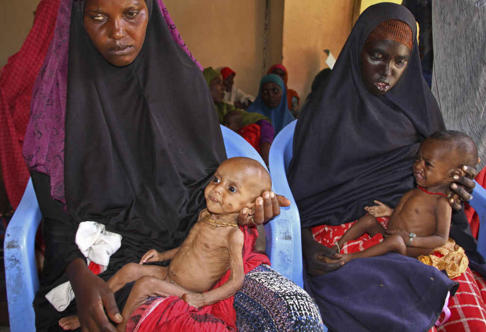 Malnourished baby Ali Hassan, left, is held by his mother, Fadumo Abdi Ibrahim, as mother Habiba Mohamed Aden holds her baby, Mohamud Ahmed, at a camp in Mogadishu.
