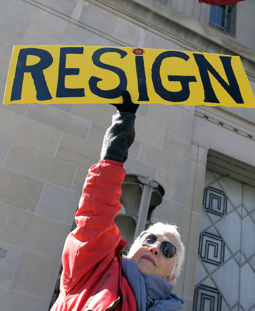 Cheryl Kreiser of Silver Spring, Md., holds up a sign outside the Justice Department in Washington, Thursday, as she joined a group to protest Attorney General Jeff Sessions.