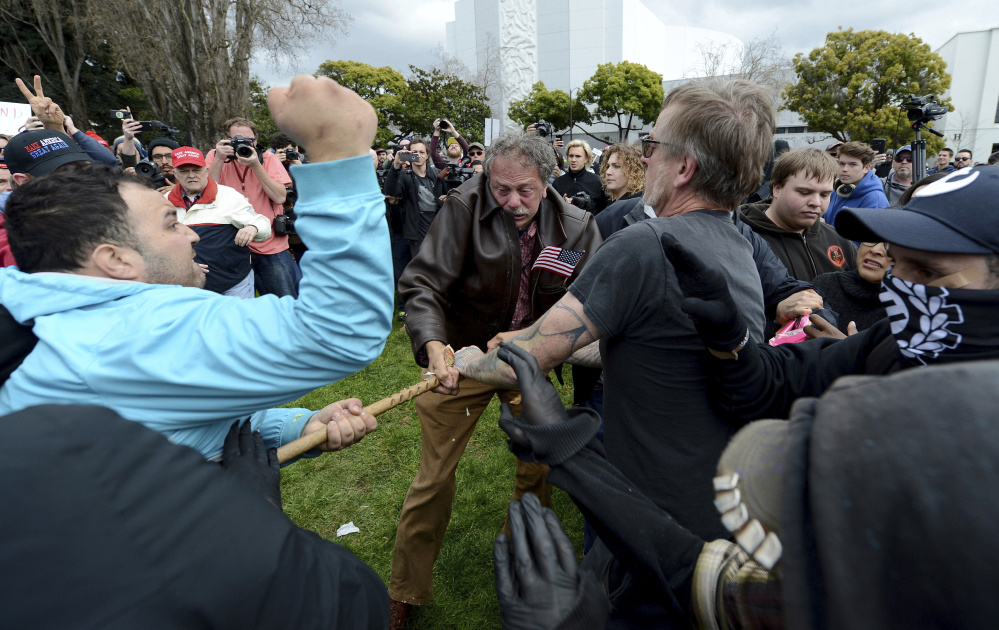Anti-Trump protesters try to take a large piece of wood away from a Trump supporter at a rally for President Trump at Martin Luther King Jr. Civic Center Park in Berkeley, Calif., on Saturday. Police in riot gear arrested at least 10 people at the rally that attracted hundreds of pro-Trump supporters and opponents at the park.
