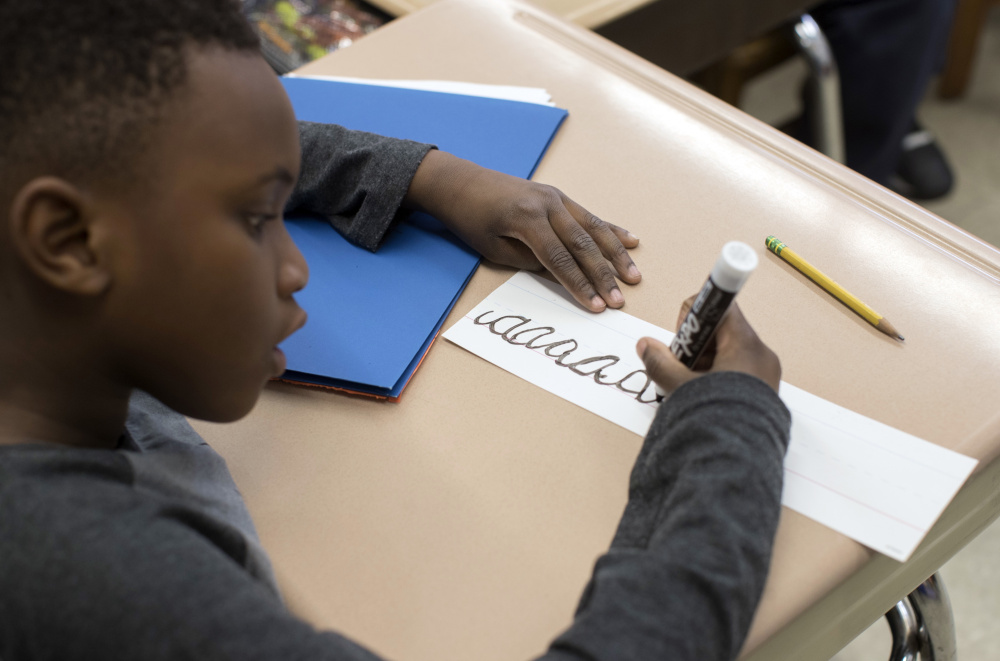 A third-grader practices his cursive handwriting at Public School 166 in the Queens borough of New York.