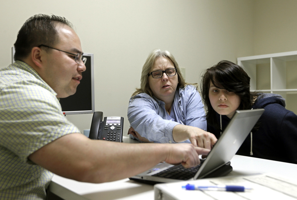 In this Feb. 12, 2015, file photo, enrollment counselor Vue Yang, left, goes over some of the plans available through the state health insurance exchange with Laura San Nicolas, center, accompanied by her daughter, Geena, while enrolling for health insurance at Sacramento Covered in Sacramento, Calif.
