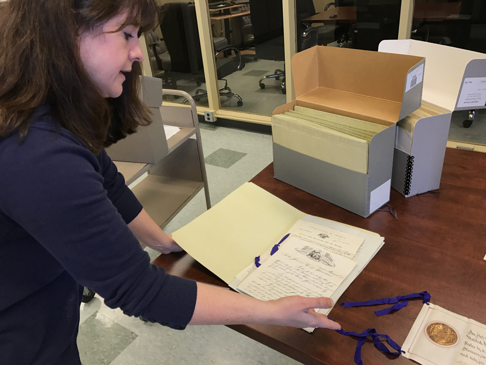 Archivist Heather Moran displays paperwork from Maine's collection of documents connected to the state's ratification of the 13th Amendment abolishing slavery in 1865. The Maine State Archives is asking for the public's help transcribing digital images of such documents.