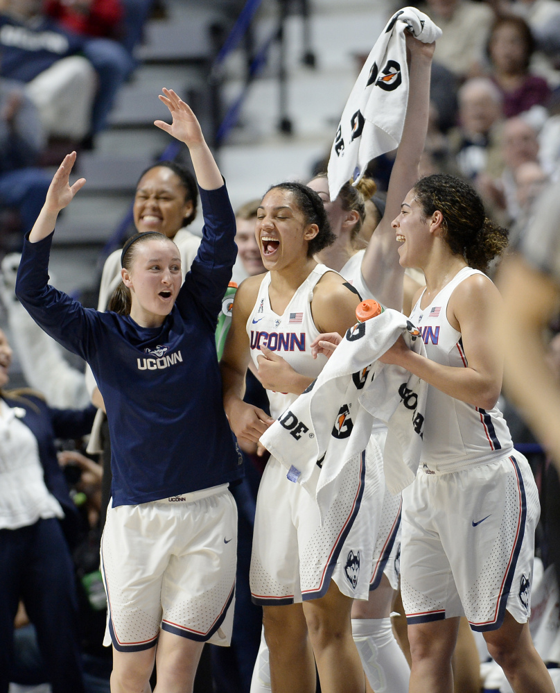 Connecticut's Tierney Lawlor, left, celebrates with Gabby Williams, center, and Kia Nurse, right, during the second half of Monday night's game against South Florida in the American Athletic Conference tournament at Uncasville, Conn.