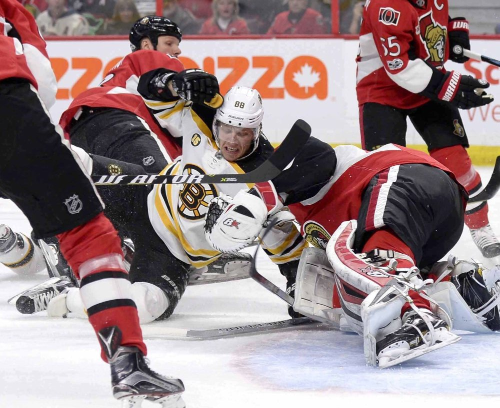 Boston's David Pastrnak, center, crashes into Ottawa goaltender Craig Anderson during the first period of the Bruins' 4-2 loss in Ottawa, Ontario.