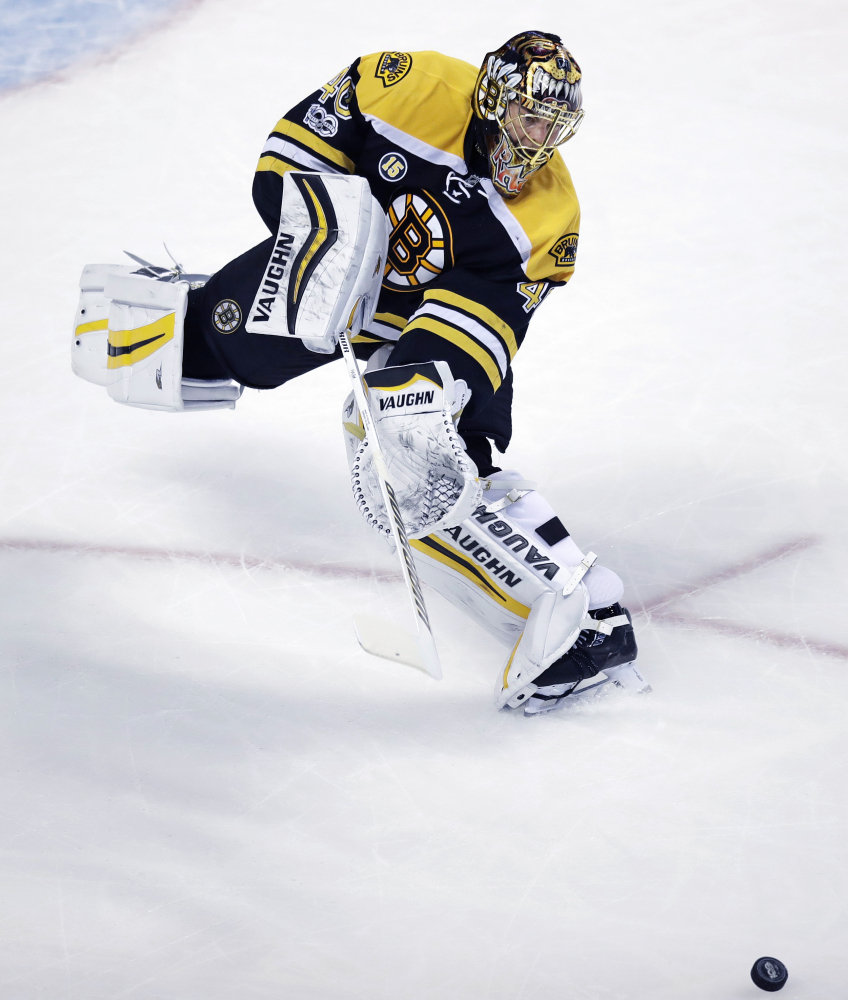 Bruins goalie Tuukka Rask skates out of the crease to clear the puck during the first period.