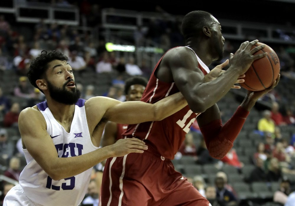 TCU's Alex Robinson, left, tries to steal the ball from Oklahoma's Khadeem Lattin during the first half of an NCAA college basketball game in the Big 12 Conference tournament Wednesday, March 8, 2017 in Kansas City, Mo. (AP Photo/Charlie Riedel)