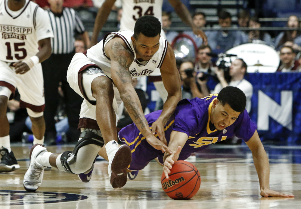 Mississippi State guard Xavian Stapleton and LSU guard Skylar Mays, right, dive for the ball during the first half of an NCAA college basketball game at the Southeastern Conference tournament Wednesday in Nashville, Tenn. (Associated Press/Wade Payne)