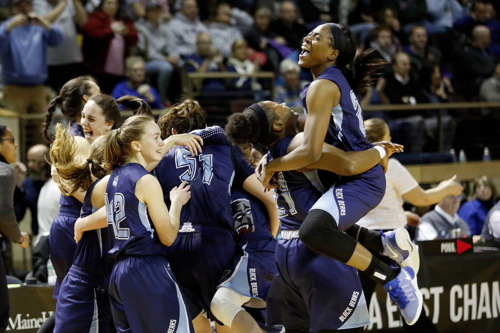 UMaine's Tanesha Sutton jumps into the arms of teammate Sheraton Jones after UMaine beat UNH in the semifinals of the America East Tournament at the Cross Insurance Arena Sunday.