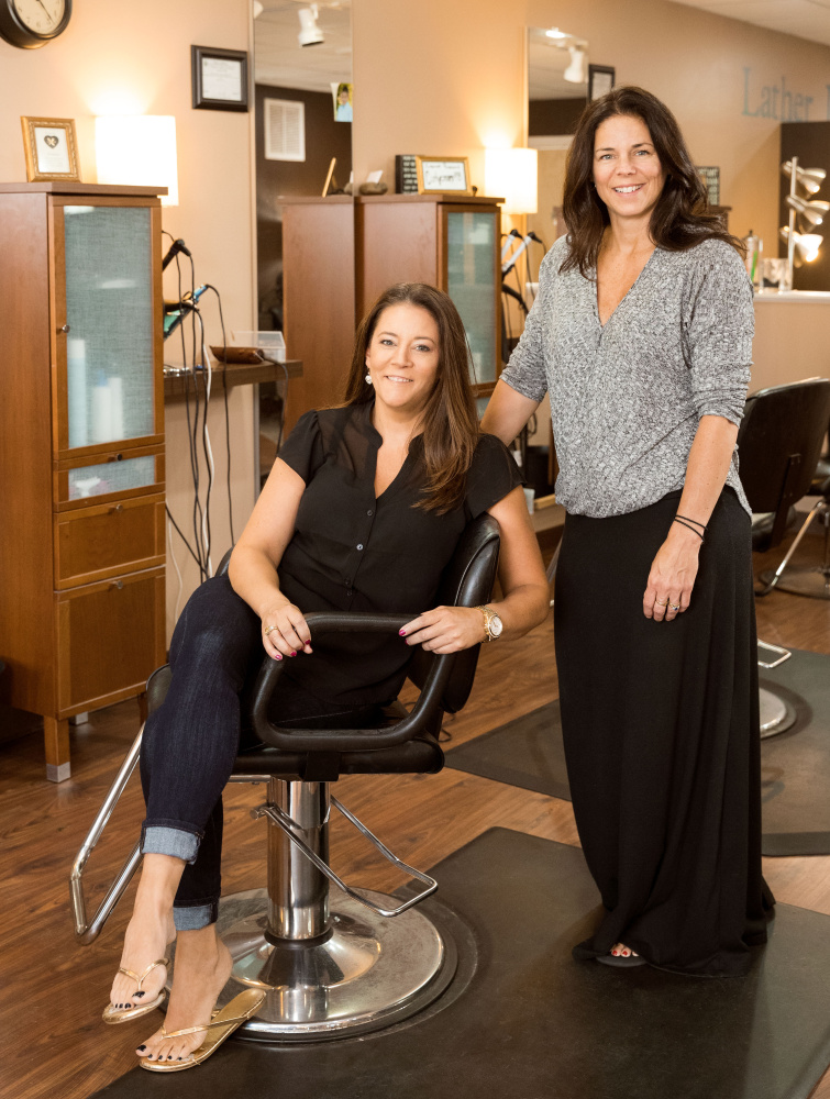 Christy Legere (sitting) and Kelly Clark at their salon in Sanford. Six of the 15 stylists at the salon have now been through the Skinny on Skin program.