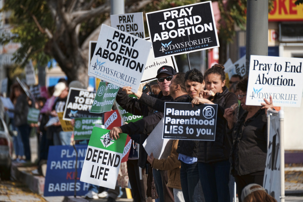 Protesters calling for Planned Parenthood to be stripped of its federal funding carry signs outside a Van Nuys, Calif., Planned Parenthood health center Feb. 11. A reader questions criticism of Planned Parenthood and other organizations that help women prevent unwanted pregnancies.