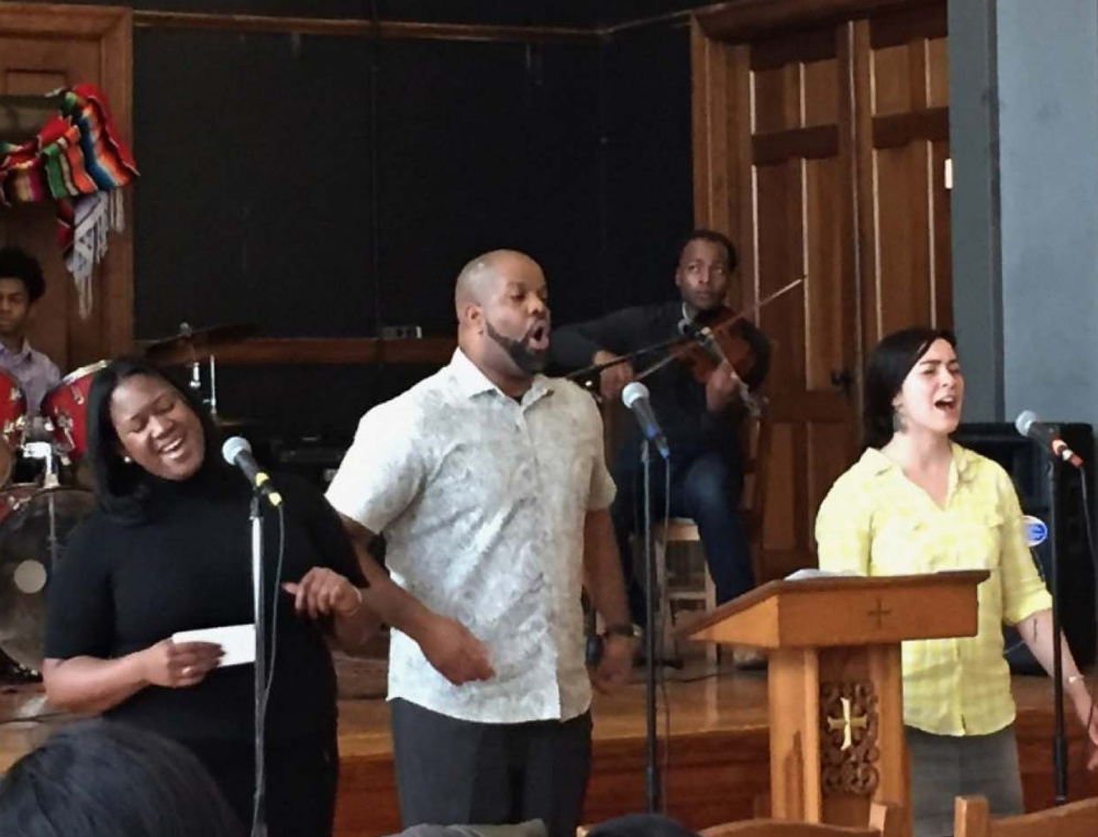"""Brittany Wells, left, Pastor Emmett Price and Hilary Davis lead a hymn at Community of Love Christian Fellowship in Boston. Davis says that when she first came to the church, she was inspired by Wells' solo rendition of """"I Love You, Lord."""""""