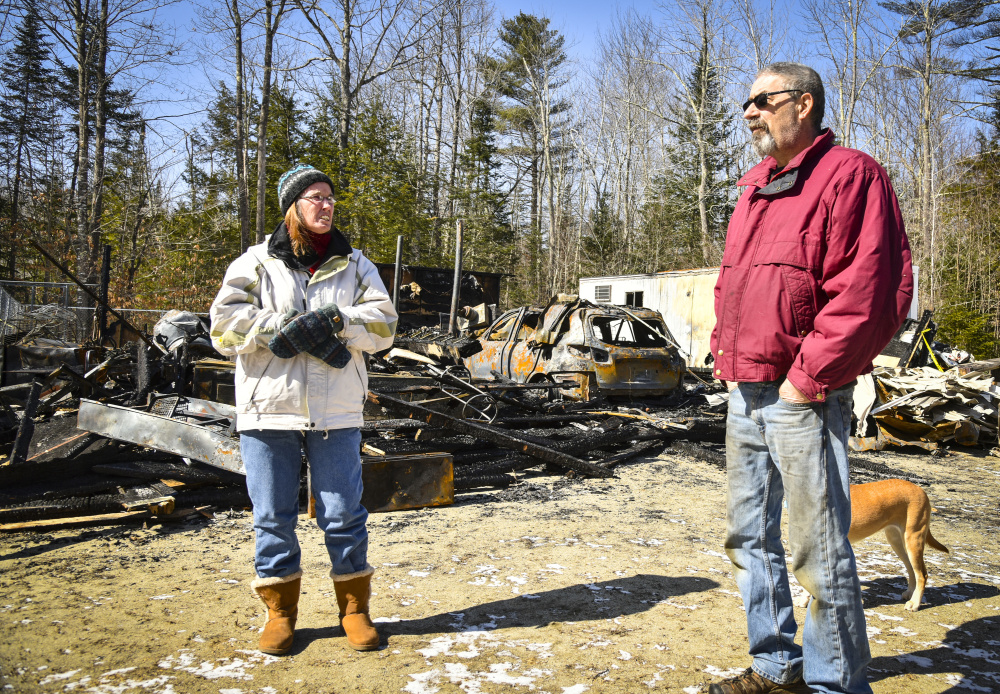 Lynn and and Paul Beaudin stand in front of the charred remains of their garage on Route 135 in Monmouth after a fire on March 2. The Beaudins are stunned at how quickly the detached garage burned but are relieved that they and their house were spared.