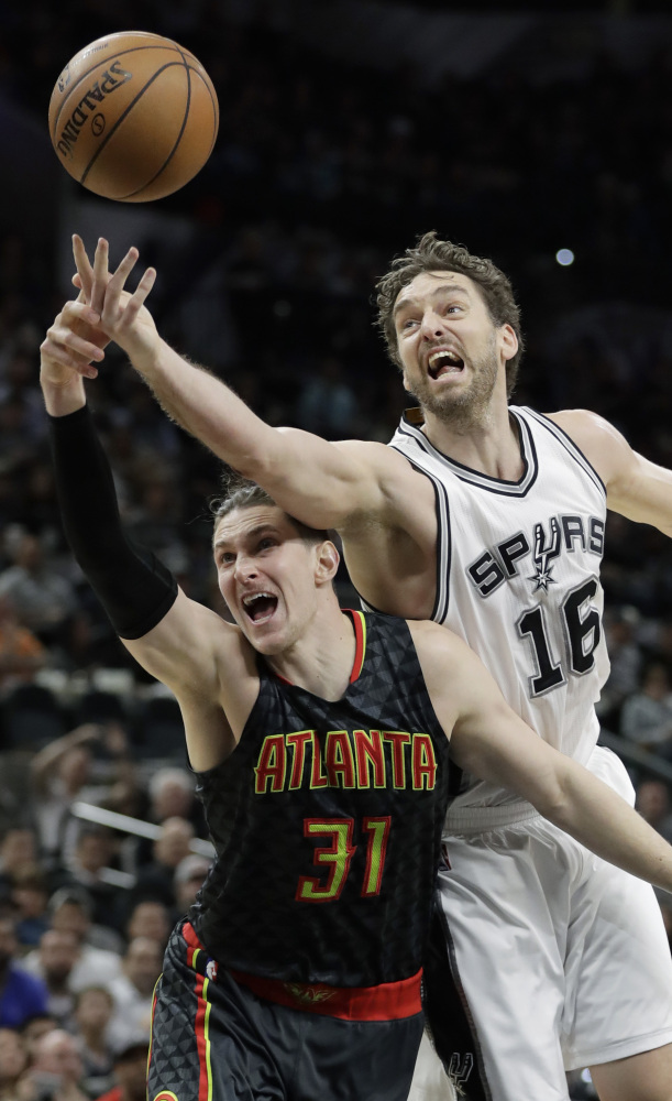 Hawks forward Mike Muscala, left, and Spurs center Pau Gasol battle for a rebound Monday in the Spurs' 107-99 win at San Antonio.