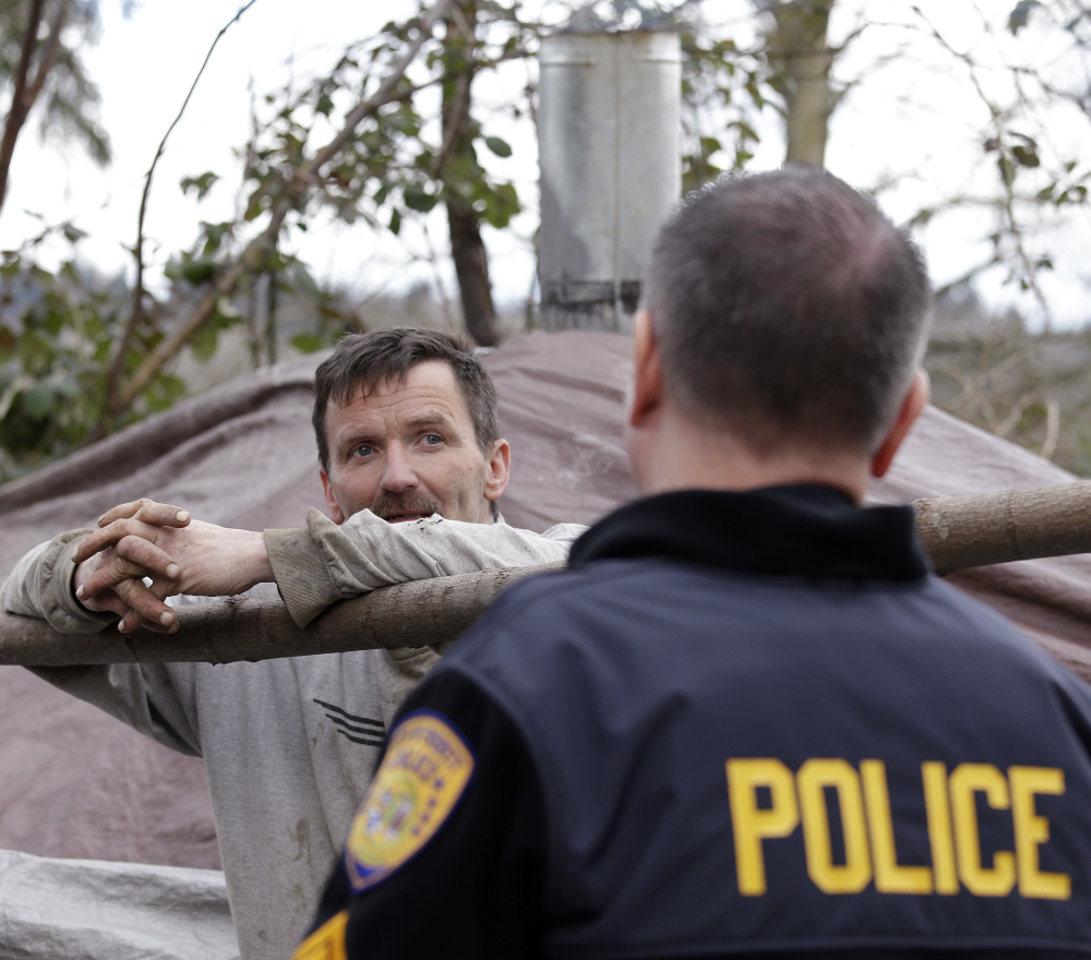 A man who lives in a shelter in the woods talks with police Sgt. Mike Braley in Everett, Wash. Braley is part of an outreach effort seeking to connect addicts with treatment.