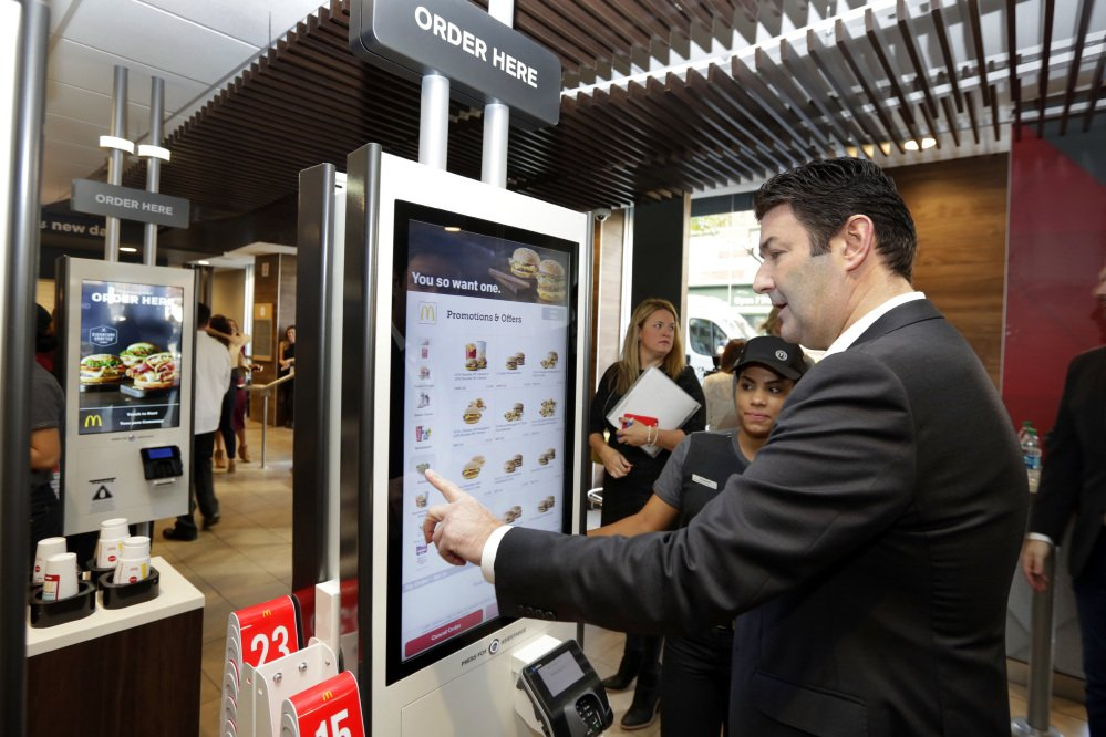 """McDonald's CEO Steve Easterbrook demonstrates an order kiosk, with cashier Esmirna DeLeon, during a presentation at a McDonald's restaurant in New York's Tribeca neighborhood last November. McDonald's has started testing mobile order-and-pay after acknowledging the ordering process in its restaurants can be """"stressful."""" The company is also introducting ordering kiosks, which it says can help ease lines at the counter and improve order accuracy."""