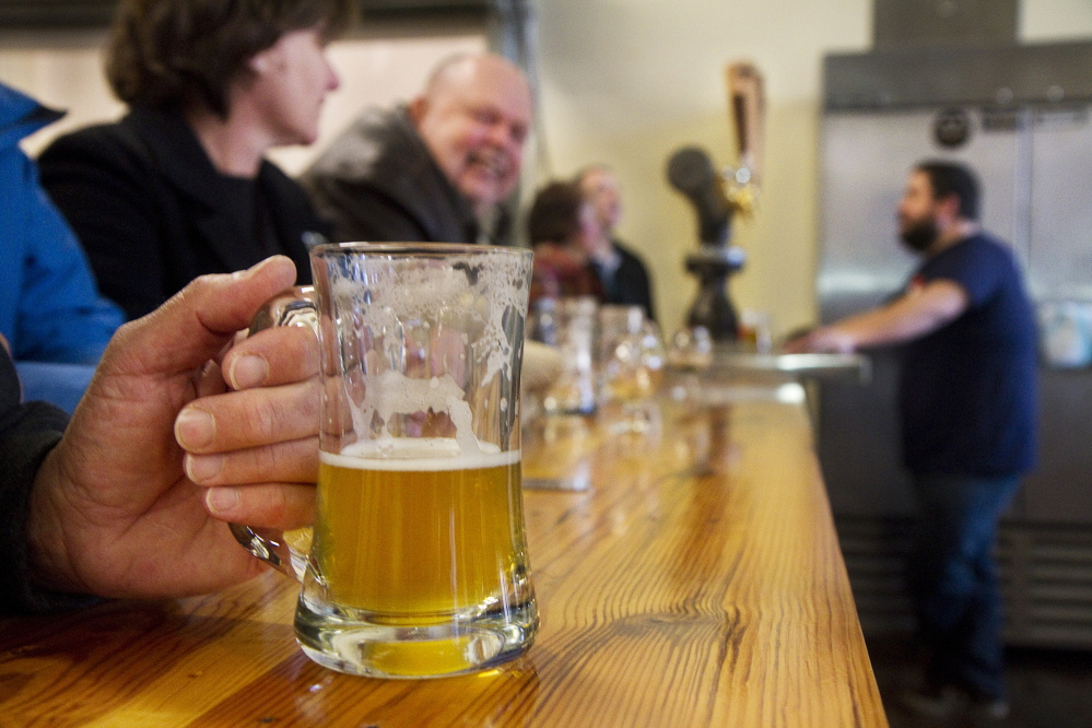 Patrons sample brews in the tasting room of Biddeford's Banded Horn Brewing Co. in 2014. Maine now has over 90 breweries, up from 34 in 2011.