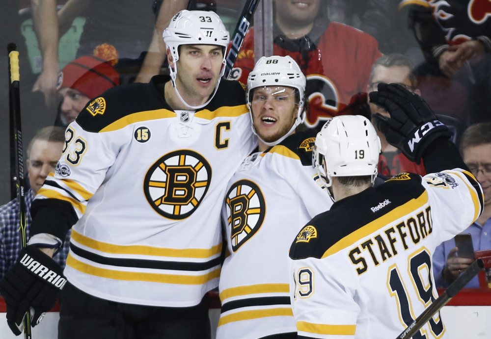 Boston's David Pastrnak, center, celebrates his goal with Zdeno Chara, left, and Drew Stafford in the first period Wednesday night in Calgary.
