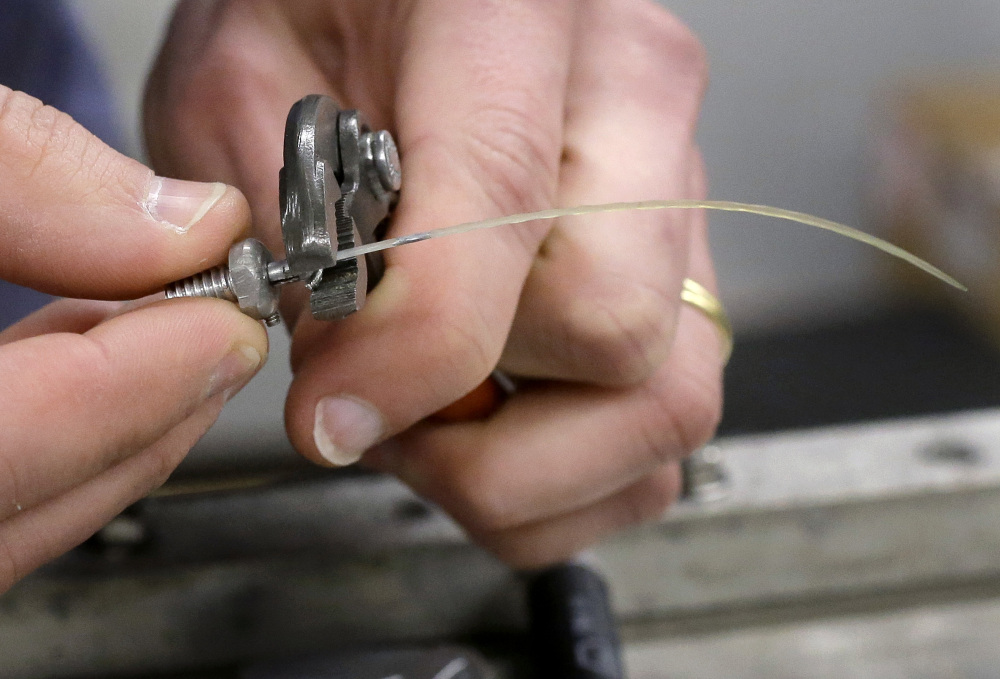 In this Thursday, March 2, 2017, photo, engineer David Wade, hands only, attaches a seal whisker to a clamp in a laboratory at the Naval Undersea Warfare Center, in Newport, R.I. Scientists think real seals, specifically their whiskers, may be the key to a new way for ships and underwater vehicles to sense their environment. (AP Photo/Steven Senne)