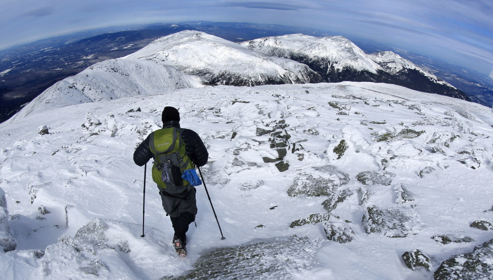 A hiker leaves the summit of Mount Washington in New Hampshire earlier this month. The snow-covered peaks of the northern Presidential Range can be seen in the distance.