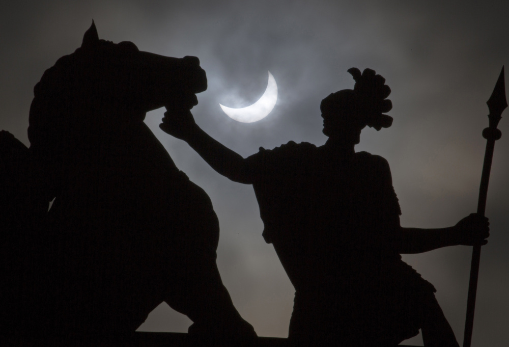 A solar eclipse in 2015 adds a dramatic flair to a statue in St. Petersburg, Russia. Weather permitting, people in a large swath of the United States will be able to see a total elipse on Aug. 21. Associated Press/ Dmitry Lovetsky