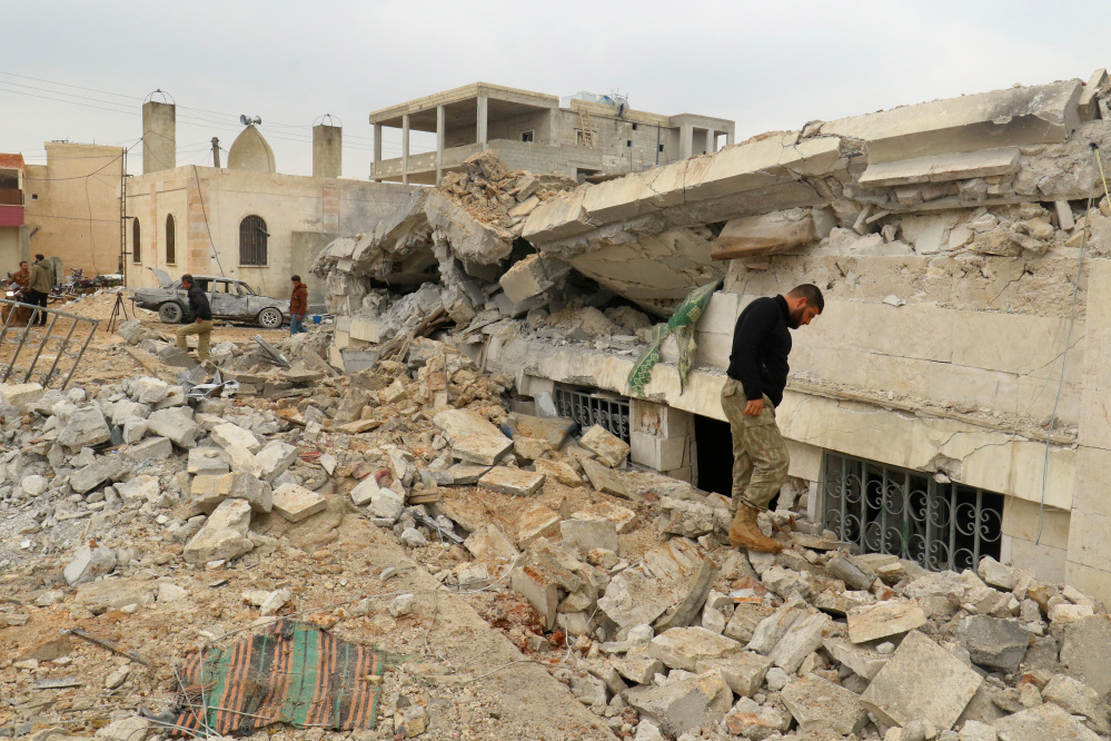 People inspect a damaged building Friday after an airstrike on the rebel-held village of Jinah, in Aleppo province in northwest Syria.