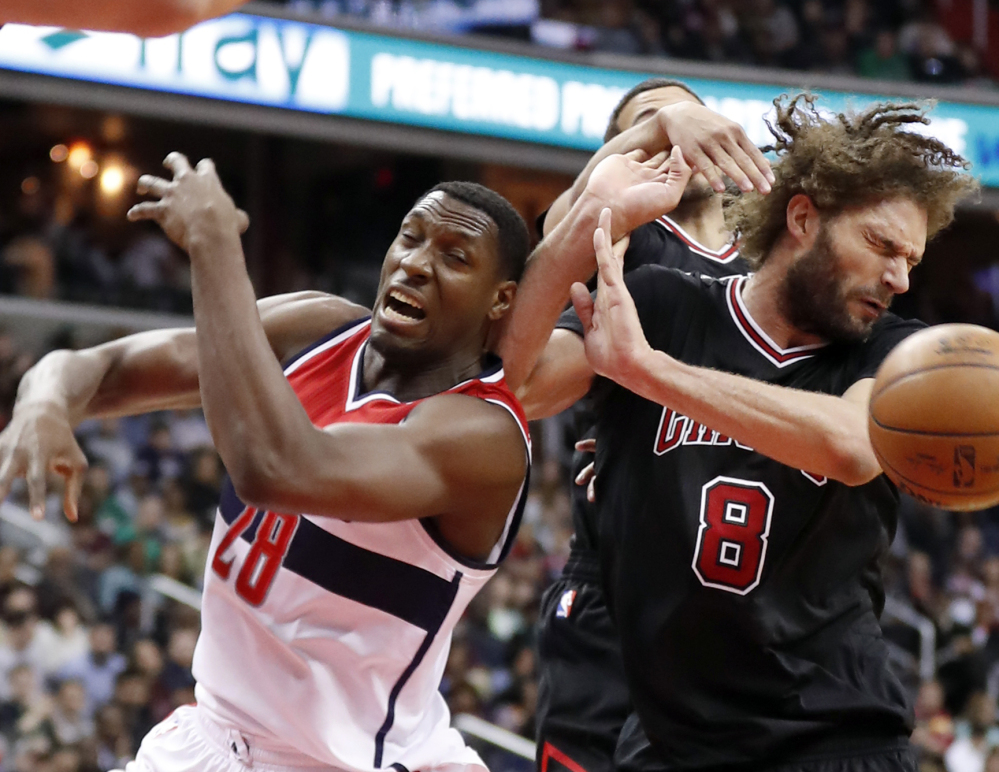 Washington center Ian Mahinmi, left, and Chicago center Robin Lopez can't find the handle on a loose ball underneath the basket during a 112-107 win by the Wizards Friday at Washington.