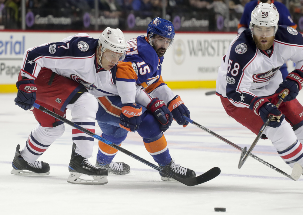 Blue Jackets defensemen Jack Johnson, left, and David Savard, right, look to keep the puck out of the reach of Islanders right wing Cal Clutterbuck during a 3-2 overtime win for Columbus Saturday in New York.
